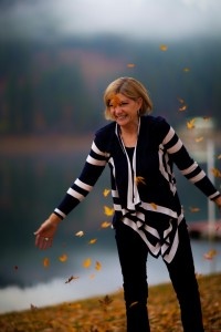 Photo of woman with fall leaves stopped in motion midair.