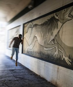 "Up in the air as he runs ""chasing"" the skinwalker image in the mural. Motion blur used on the arm & leg in back. there is a large painting so that art is most of the image."