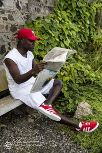 A casual fashion look for reading the daily news. Red sneakers, red hat and white top and shorts.