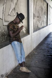 Benjamin in one of Spokane's mural underpasses. He is posing in front of large scale art and shows his fashion with a had and high top shoes, short jeans.