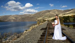 This wide shot features a bride on her journey...posed on the train tracks that follow the Snake River.