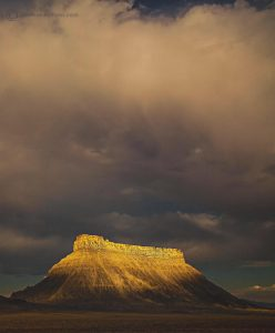 Factory Butte UT with gold light on top of the butte and dramatic clouds with gold light as well