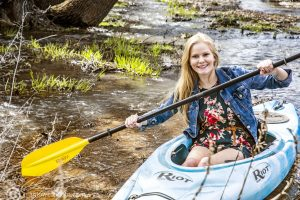 blonde model in a blue kayak on a small creek with a yellow paddle.