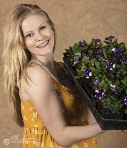 Blonde model in yellow dress holding a flat of Night Sky petunias