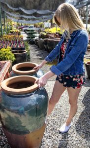 Blonde model in short dress shopping for pottery, looking at 2 large pots.