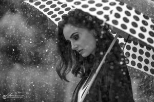 polka dot umbrella. Black and white photo of brunette staying dry under the downpour.